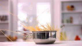 Spaghetti falling into pot in kitchen stock footage