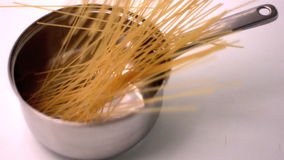 Spaghetti falling in a pot. In slow motion stock video