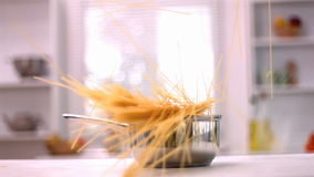 Spaghetti falling in a saucepan in kitchen. In slow motion stock video footage