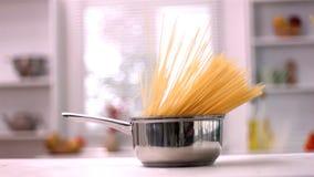 Spaghetti falling in saucepan in kitchen. In slow motion stock video