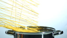 Spaghetti falling into a saucepan. In slow motion stock footage