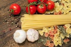 Spaghetti, farfalle , cherry tomatoes and garlic Royalty Free Stock Image