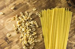 Spaghetti and figurines on a wooden background. Top view Royalty Free Stock Photo