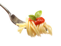 Spaghetti on a fork. Cleanly isolated spaghetti swirled onto a fork with sauce and basil leaves Stock Photo