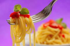 Spaghetti on a fork. Spaghetti with sauce and mint on a fork with unfocused background Stock Photos
