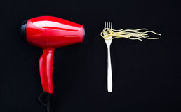 Spaghetti on a fork and a hairdryer. Fun concept with a hairdryer blowing on a fork with spaghetti, isolated on a black background Royalty Free Stock Images