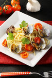 Spaghetti with fresh clams and tomato. On complex background Royalty Free Stock Photo