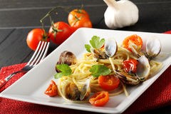 Spaghetti with fresh clams and tomato. On complex background Stock Photography