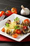 Spaghetti with fresh clams and tomato. On complex background Royalty Free Stock Images