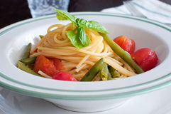 Spaghetti with fresh green beans and cherry tomatoes Stock Photos
