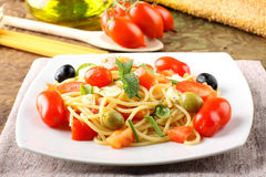 Spaghetti with fresh tomatoes, olives and mint. On complex background Stock Images