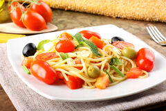 Spaghetti with fresh tomatoes, olives and mint Stock Image