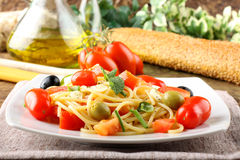 Spaghetti with fresh tomatoes, olives and mint. On complex background Royalty Free Stock Images