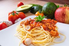 Spaghetti and fresh tomatoes with seasonings on wooden boards. royalty free stock photos