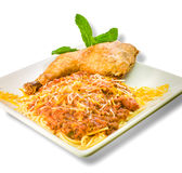 Spaghetti with fried chicken and sliced sausage link corner view Stock Photos