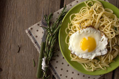 Spaghetti with fried egg and rosemary on green plate Royalty Free Stock Image
