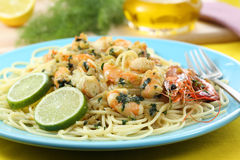 Spaghetti with fried shrimps and some drops of lime Royalty Free Stock Images