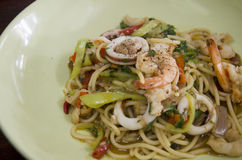 Spaghetti fried spicy mixed seafood with chilli and Basil leaves royalty free stock photography