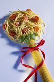 Spaghetti Fun. Cooked and uncooked spaghetti shaped as a flower and tied with a red ribbon Stock Image