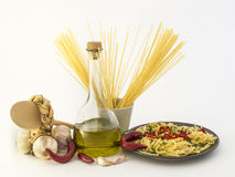 Spaghetti, garlic, olive oil, red pepper. Plate of spaghetti with garlic, olive oil, chili pepper on white background Stock Photos