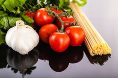 Spaghetti garlic parsley and tomatoes. A bunch of spaghetti, some cherry tomatoes, parsley and garlic on a dark surface Royalty Free Stock Photos