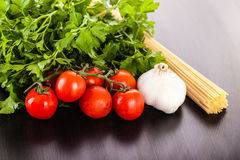 Spaghetti garlic tomatoes and parsley. A bunch of spaghetti, some cherry tomatoes, parsley and garlic on a dark surface Stock Photos
