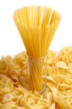 Spaghetti in glass. Standing on several types of pasta Royalty Free Stock Photo