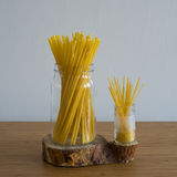 Spaghetti in glass jar. Macaroni in glass bank on wooden stand on bamboo table Royalty Free Stock Photography