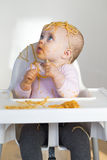 Spaghetti Head. Little baby girl sat in highchair covered in food from lunch stock photos