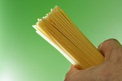 Spaghetti in humand hand on green background Stock Image