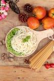 Spaghetti i surowy spaghetti na drewnianym tle Fotografia Stock