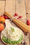 Spaghetti i surowy spaghetti na drewnianym tle Zdjęcia Royalty Free