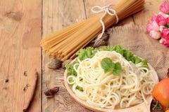 Spaghetti i surowy spaghetti na drewnianym tle Fotografia Royalty Free