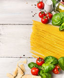 Spaghetti ingredients for cooking witj oil,tomatoes and basil on white wooden background, top view Royalty Free Stock Photography