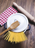Spaghetti inside a pot next to a wooden fork and a roller. Stock Photos