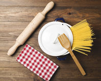Spaghetti inside a pot next to a wooden fork and a roller on wooden table. Stock Photo