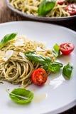 spaghetti Italiaanse deegwarenspaghetti met de kersentomaten van basilicumpesto en olijfolie Stock Foto's