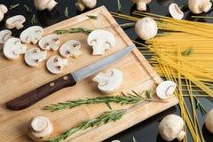 Spaghetti italiani con i funghi sulla tavola nera Immagini Stock