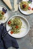 Spaghetti italiani con il pesto, le erbe ed i pomodori ciliegia al piatto bianco fotografie stock libere da diritti