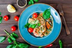Spaghetti italiani della pasta con frutti di mare, langoustine, cozze, calamaro, pettini, gamberetto, parmigiano fotografie stock libere da diritti