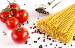 Spaghetti kłamstwo na białym tle wraz z czereśniowymi pomidorami, łyżką i rozwidleniem, obrazy royalty free