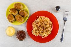 Spaghetti with ketchup, cutlets, pepper, sauces in bowl and fork Royalty Free Stock Photos