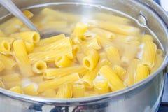 Spaghetti in kokend water op een gasfornuis wordt gekookt dat Het traditionele Italiaanse voedsel stock fotografie