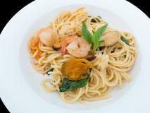 Spaghetti kruidig met zeevruchten op een witte die plaat op de zwarte achtergrond met het knippen van weg wordt geïsoleerd royalty-vrije stock afbeelding