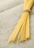 Spaghetti legati con la corda su insaccamento organico Fuoco selettivo immagini stock libere da diritti