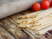 Spaghetti lie on a wooden table Stock Photo