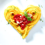 Spaghetti For A Loved One. Spaghetti with tomato and cheese sauce garnished with basil arranged in coils into a heart shape for love Royalty Free Stock Photo
