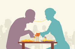 Spaghetti lovers. Colorful editable  silhouette of lovers eating spaghetti together in a restaurant Royalty Free Stock Images