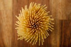 Spaghetti lunghi gialli su un fondo di legno, vista superiore Pasta italiana gialla Spaghetti lunghi Spaghetti crudi bolognese fotografia stock