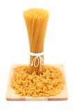 Spaghetti and macaroni. On wooden board Stock Photos